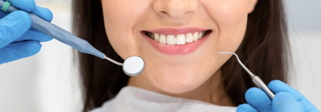 Close up of smiling woman attenting dental clinic